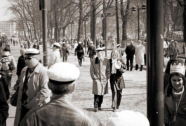Ihmisiä kävelemässä kadulla, ylioppilaslakki päässään.
