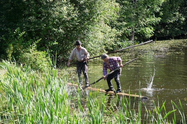 Kaksi miestä tasapainottelee uivalla tukilla