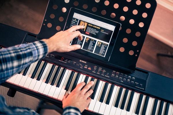 Mies käyttää Rockway-kurssia tabletilla ja soittaa samalla pianoa.